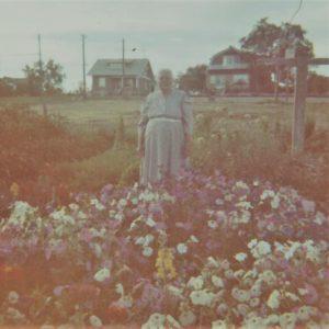 In front of her flower garden